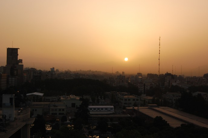 The sun hangs low over the city of Tehran